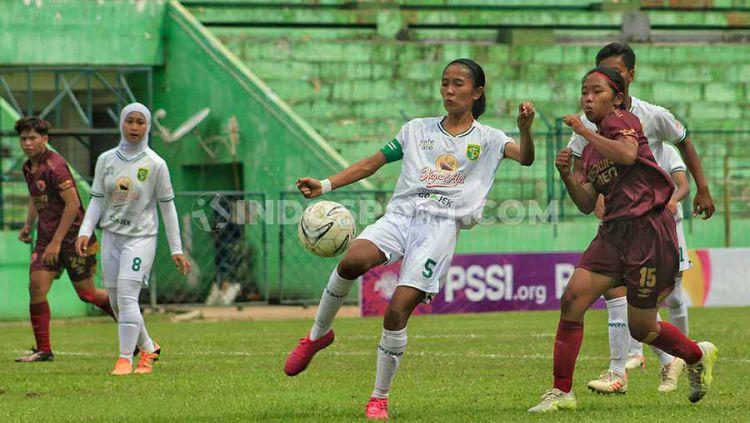 Pemain Persebaya putri Feni Norrahma berusaha menghalangi pemain PSM Makassar Sulfiati, Selasa (19/11/19) dalam laga Liga 1 putri. Copyright: © Fitra Herdian/INDOSPORT