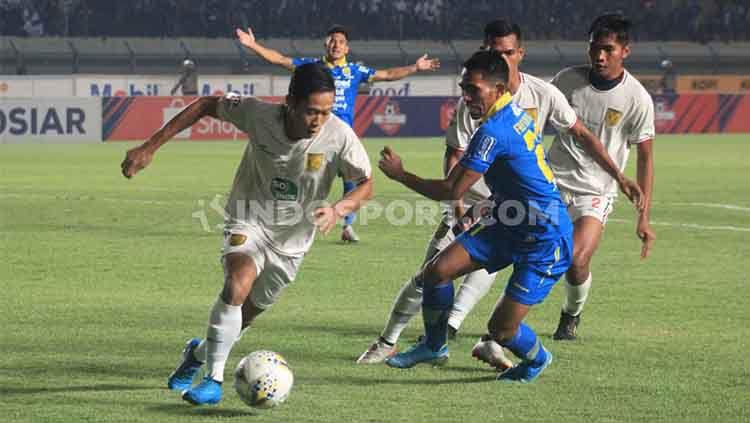 Pemain Persib Bandung, Frets Butuan mencoba mengejar pemain Persela Lamongan pada pertandingan Liga 1 2019 di Stadion Si Jalak Harupat, Kabupaten Bandung, Selasa (03/12/2019). Copyright: © Arif Rahman/INDOSPORT