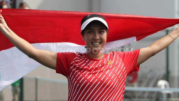 Aldila Sutjiadi mengibarkan bendera Indonesia usai meraih medali emas tenis SEA Games 2019 dari nomor tunggal putri. Copyright: © Ronald Seger Prabowo/INDOSPORT