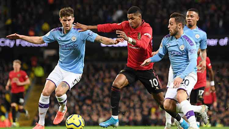 John Stones (kiri) saat berduel di laga Manchester United vs Manchester City. Copyright: © Michael Regan/GettyImages