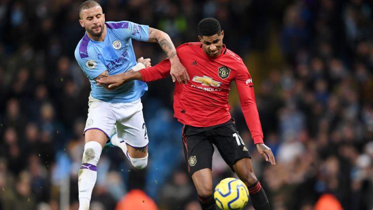 Kyle Walker saat berduel dengan Marcus Rashford di laga Manchester City vs Manchester United. Copyright: © Laurence Griffiths/Getty Images