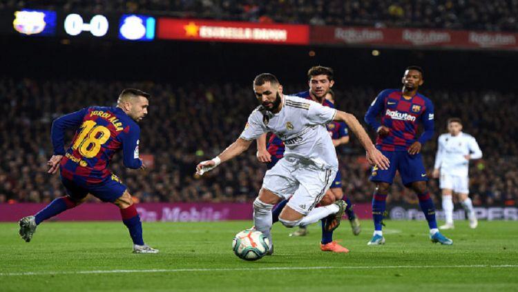Karim Benzema berusaha melewati Jordi Alba pada laga Barcelona vs Real Madrid, Kamis (19/12/19). Copyright: © Alex Caparros/Getty Images
