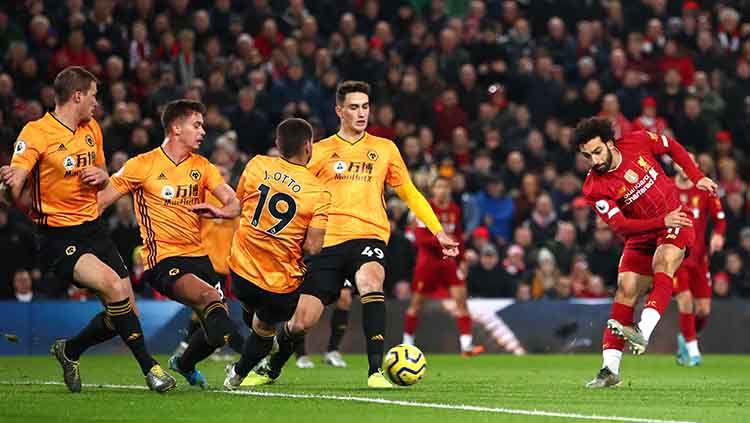 Mohamed Salah melepaskan tendangan tapi dihadang pemain Wolverhampton Wanderers. Copyright: © Twitter.com/@LFC