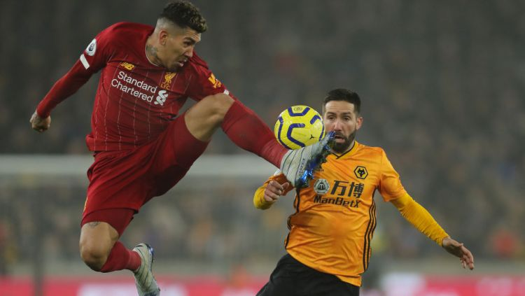 Striker Liverpool, Roberto Firmino, saat menahan bola di depan pemain Wolves, Joao Moutinho Copyright: © Matthew Ashton - AMA/Getty Images