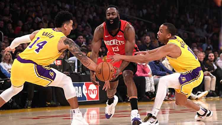 Pemain megabintang NBA, James Harden (tengah-Houston Rockets) dijaga ketat oleh dua pemain LA Lakers. Copyright: © Kevork Djansezian/Getty Images