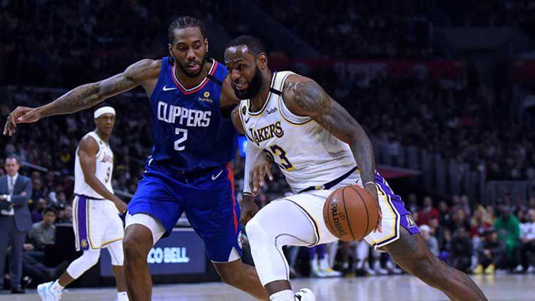 Pemain bintang LA Clippers, Kawhi Leonard (kiri) berduel dengan bintang LA Lakers, LeBron James. Copyright: © Harry How/GettyImages