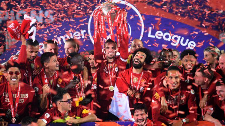 Jordan Henderson mengangkat trofi Liga Primer Inggris bersama skuat Liverpool Copyright: © Laurence Griffiths/PA Images via Getty Images