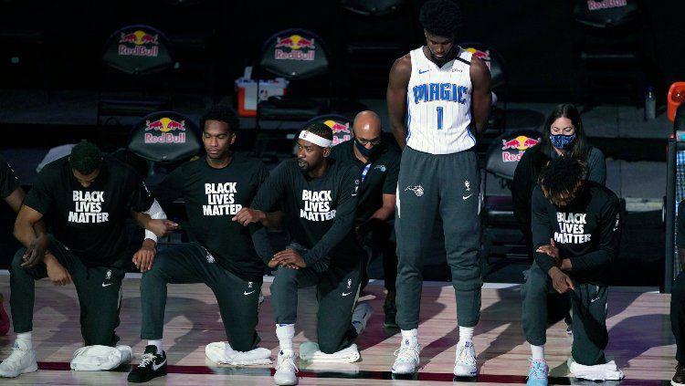 Bintang Orlando Magic, Jonathan Isaac menjadi satu-satunya pemain NBA yang berdiri selama lagu kebangsaan AS sebelum pertandingan melawan Brooklyn Nets. Copyright: © Ashley Landis - Pool/Getty Images