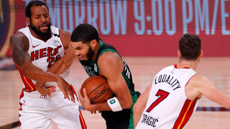 Pemain Boston Celtics Jayson Tatum diadang dua pemain Miami Heat dalam laga NBA, Sabtu (26/09/20). Copyright: © Mike Ehrmann/Getty Images