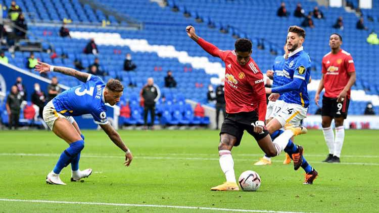 Striker Manchester United, Marcus Rashford melepaskan tendangan kaki kirinya ke gawang Brighton. Copyright: © Glyn Kirk - Pool/Getty Images