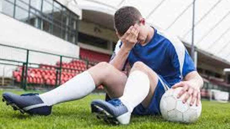 Ilustrasi pemain sepak bola sakit kepala. Copyright: © hellosehat