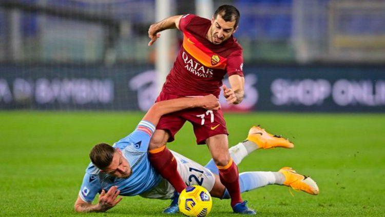 Henrikh Mkhitaryan terlibat duel sengit dengan Sergej Milinkovic-Savic dalam duel AS Roma vs Lazio Copyright: © Twitter @OfficialASRoma