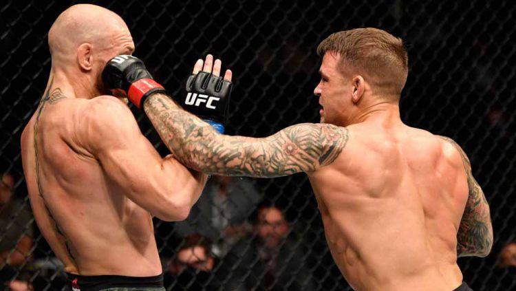 Petarung UFC Conor McGregor mendapat pukulan keras dari Dustin Poirier dalam pertarungan UFC Fight Island di Abu Dhabi, Uni Emirat Arab. Copyright: © Jeff Bottari/Zuffa LLC via Getty Images