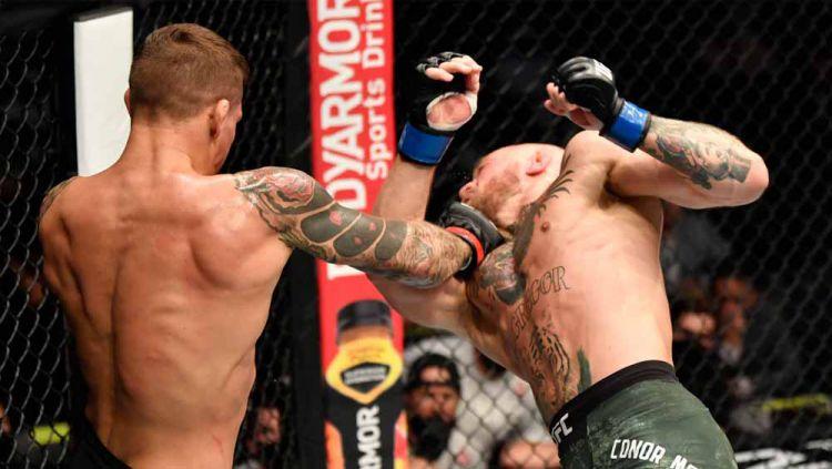 Petarung UFC Dustin Poirier mengarahkan pukulan keras ke wajah Conor McGregor dalam pertarungan UFC Fight Island di Abu Dhabi, Uni Emirat Arab (ilustrasi MMA). Copyright: © Jeff Bottari/Zuffa LLC/Getty Images