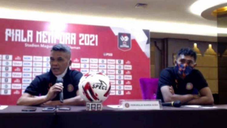 Pelatih Persiraja, Hendri Susilo (kiri), didampingi pemainnya, Fery Komul (kanan), dalam temu pers jelang pertandingan, Selasa (23/3/21). Copyright: © zoom meeting Piala Menpora 2021 Grup D