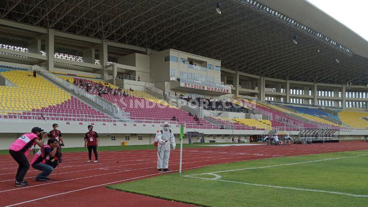 Indosport - Salah satu penerapan protokol kesehatan Piala Menpora 2021 di Stadion Manahan Solo, yakni petugas menyemprotkan cairan disinfektan di tiang tendangan sudut.