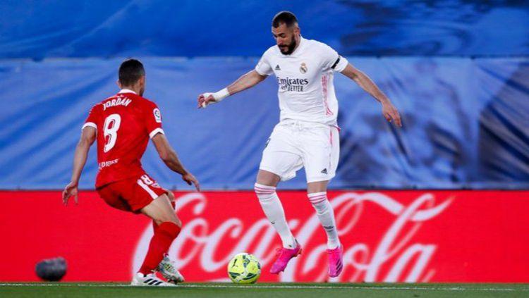 Karim Benzema (Real Madrid) sedang mencoba untuk melewati hadangan Joan Jordan (Sevilla) Copyright: © Twitter @realmadrid