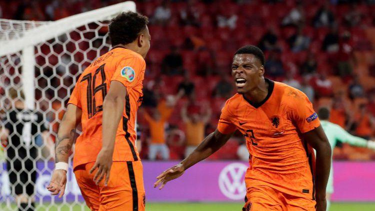 Denzel Dumfries merayakan gol kedua Belanda atas Austria bersama Donyell Malen dalam laga lanjutan Grup C Euro 2020, Jumat (18/06/21). Copyright: © Eric Verhoeven/Soccrates/Getty Images