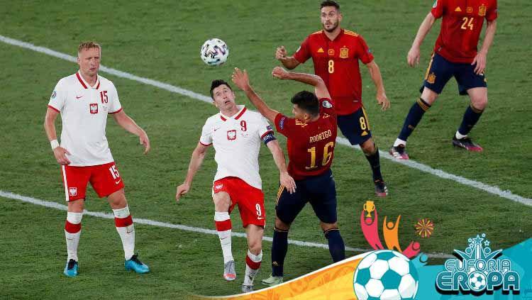 Robert Lewandowski berduel dengan Rodrigo di laga Euro 2020 Spanyol vs Polandia. Copyright: © Jose Manuel Vidal/Getty Images