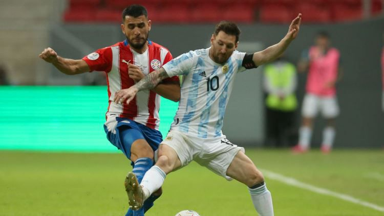 Junior Alonso dan Lionel Messi bertarung di laga Copa America Argentina vs Paraguay, Selasa (22/06/21) pagi WIB. Copyright: © Alexandre Schneider/Getty Images