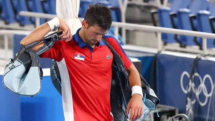 Novak Djokovic asal Serbia meninggalkan lapangan tenis setelah kalah dalam pertandingan semifinal melawan Alexander Zverev dari Jerman. Copyright: © REUTERS/Mike Segar