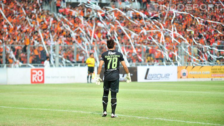 Kiper Persib, I Made Wirawan, melihat ke arah pendukung Persija yang melempar gulungan kertas ke arah lapangan pada pertandingan Persija vs Persib di SUGBK, Minggu (10/08/14). Copyright: © Ratno Prasetyo/ INDOSPORT